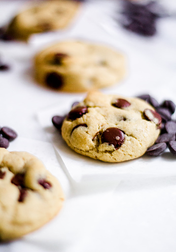 Chocolate chip cookie with vanilla dough on an white surface with glass of milk