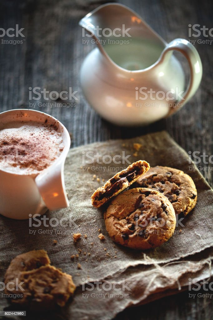 Chocolate chip cookies and cup of coffee on wooden table. stock photo