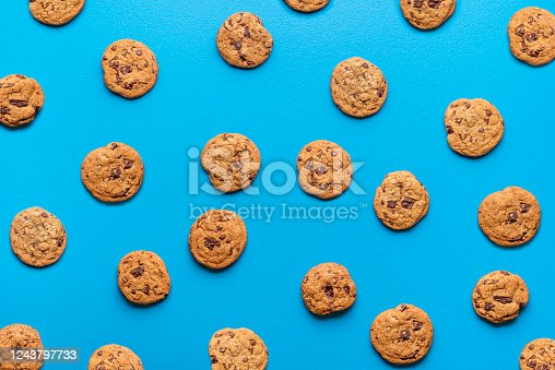 istock Chocolate chip cookies background. Cookies pattern on blue color 1243797733