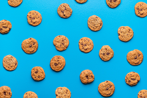 Brown chocolate chip cookies background on a vibrant blue backdrop. Flat lay with cookies pattern. Sweet treats background. Many choco snacks.