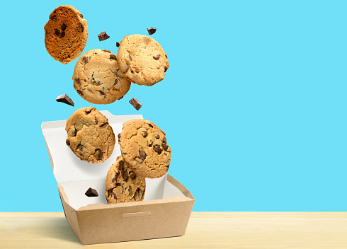 Chocolate chip cookies falling in paper box over turquoise blue background. Copy space