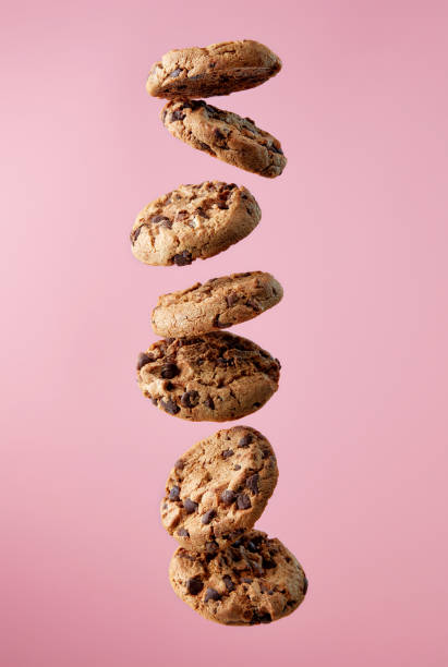Chocolate chip cookies falling in stack Chocolate chip cookies falling, pink background, food levitation cookie stock pictures, royalty-free photos & images
