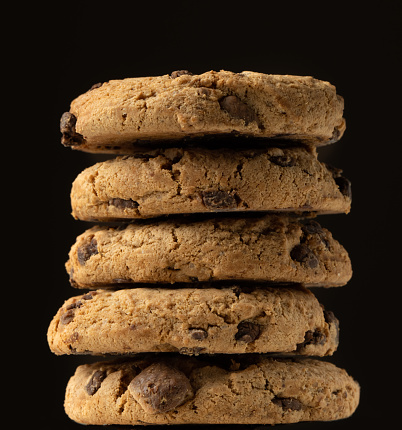 Side view of stacked chocolate chip cookies against black background