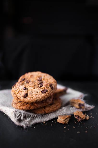 """schokoladenkekse auf dunklen mit platz für text, frisch gebacken. selektiven fokus mit textfreiraum. haufen von choco cookie """"n - hafer cookies stock-fotos und bilder"""