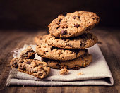 Chocolate chip cookies on linen napkin wooden table.