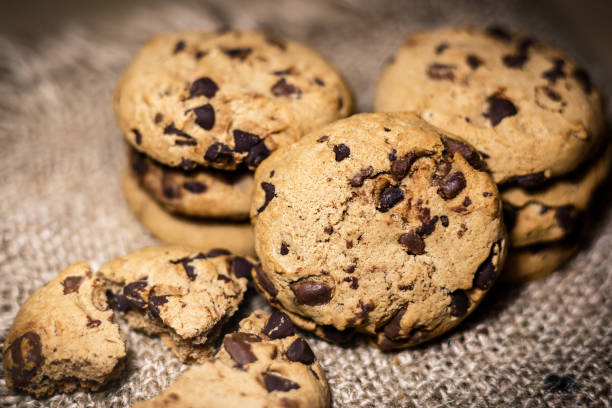 Chocolate chip cookies on rustic background Fresh Chocolate chip cookies, freshly baked on rustic background. Close-up view with selective focus. chocolate chip cookie stock pictures, royalty-free photos & images