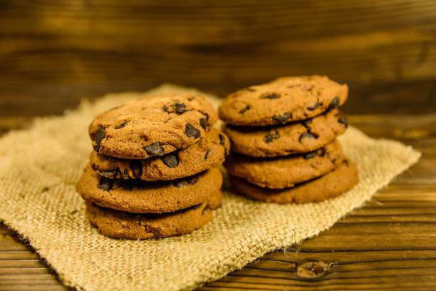 chocolate chip cookies auf sackleinen auf einem holztisch - low carb kekse stock-fotos und bilder