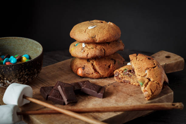 Chocolate chip cookies or biscuits, chocolate, eggs and flour on dark woodenboard with black background, front view stock photo
