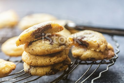 Freshly baked American cookies with chocolate chips on a cooling rack.