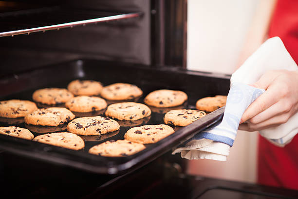 chocolate chip cookies chocolate chip cookies on baking pan hot out of the oven close up oven stock pictures, royalty-free photos & images