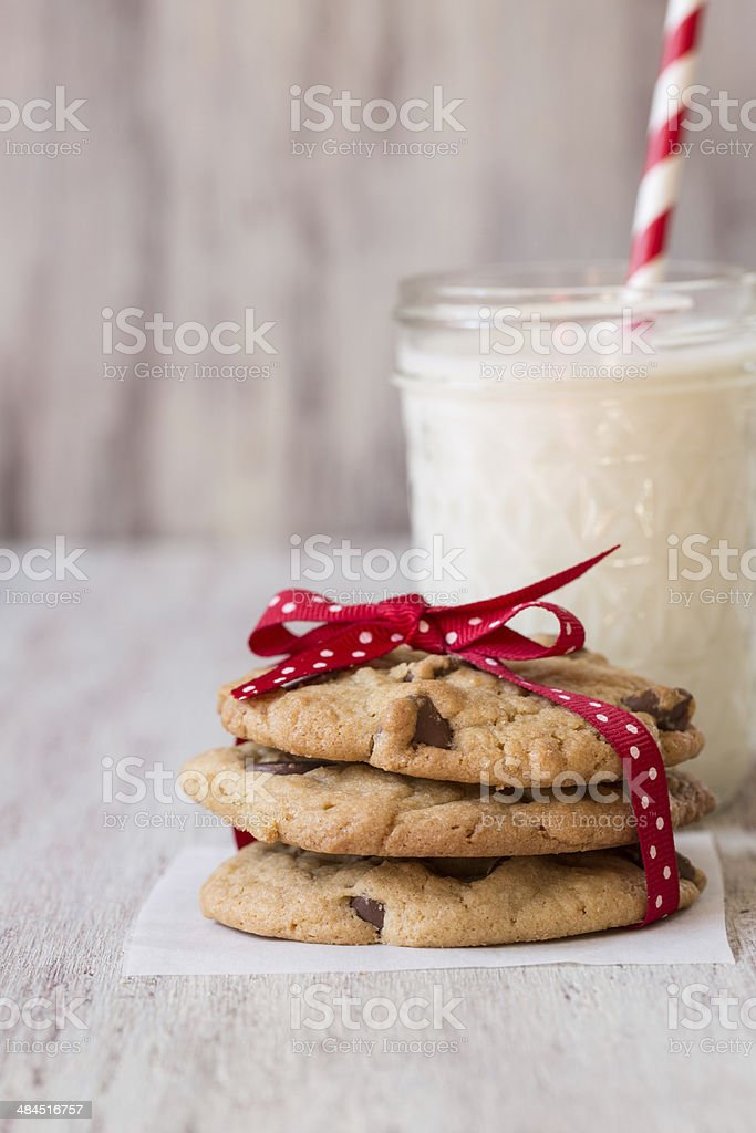 Chocolate Chip Cookies Tied With Ribbon and Glass of Milk stock photo
