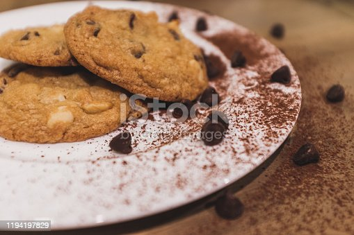 Baked chocolate chip cookies plated with cocoa dusting and morsels