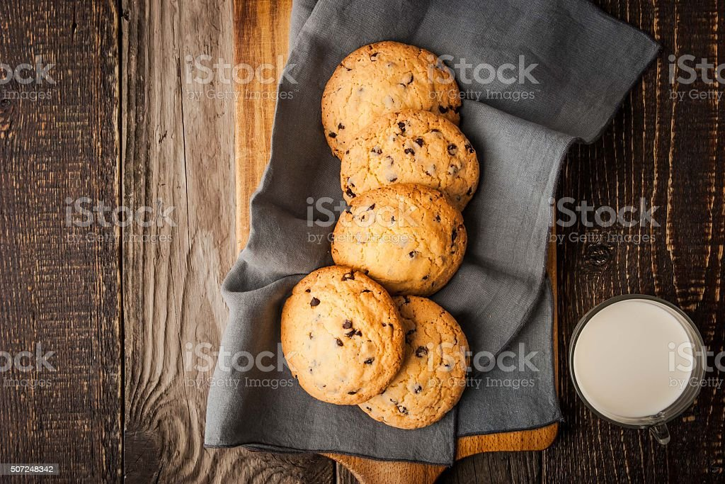 Chocolate chip cookies  with milk on wooden table top view stock photo