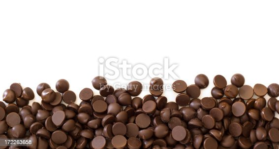Subject: Chocolate chips, a common baking ingredient, forming the bottom border of the frame. Designed for page layout with white copy space on the top half of the page.