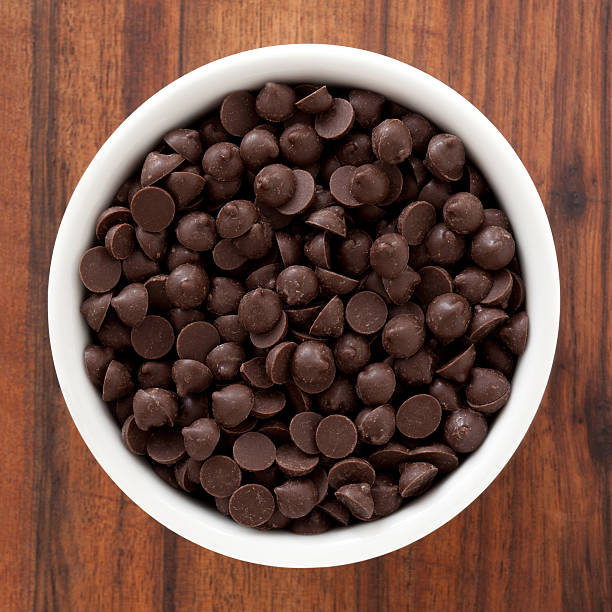 Chocolate chips Top view of white bowl full of chocolate chips chocolate chip cookie stock pictures, royalty-free photos & images