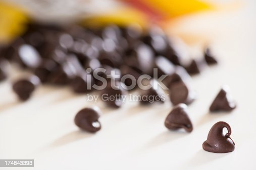 A bag of chocolate chips pouring out onto the countertop.  Very shallow depth of field with focus on the front most chip.  Copy space in the lower left.More of this Series:
