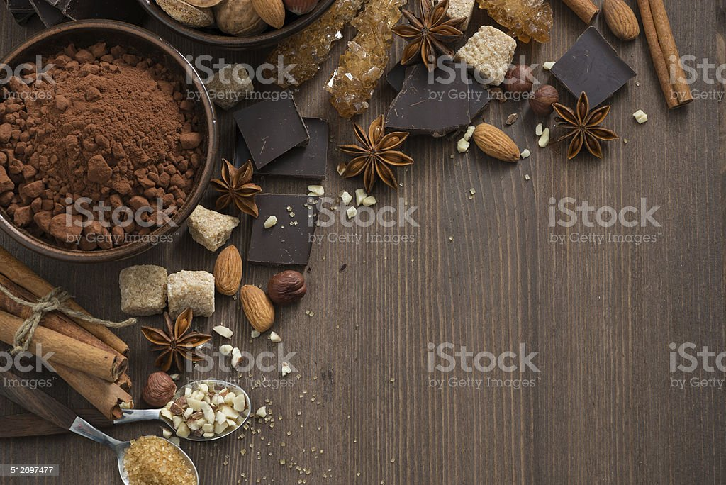 chocolate, cocoa, nuts and spices on wooden background, top view stock photo