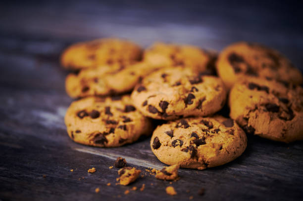 chocolate cookies lying side by side on wooden background stock photo