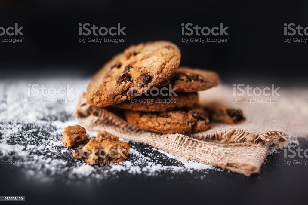 Chocolate cookies on linen napkin on black background. Chocolate chip...