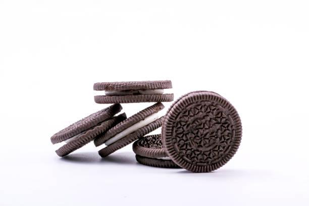 Cookies de chocolate com recheio cremoso, isolado no fundo branco. - foto de acervo