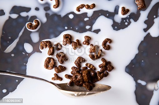 istock Chocolate cornflakes in the shape of letters of the English alphabet for a quick breakfast with milk on a gray background 1160993567