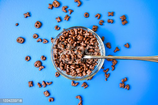 511983702 istock photo Chocolate cornflakes in the shape of letters of the English alphabet for a quick breakfast on blue background, Close up in spoon 1224220718