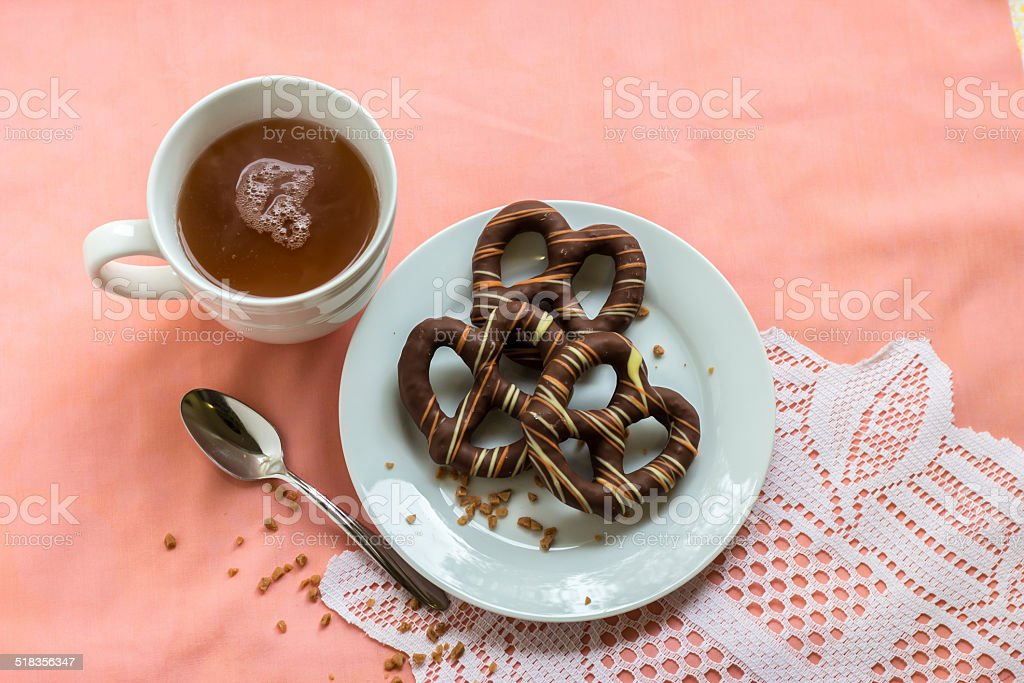 chocolate covered pretzels with cup of tea stock photo