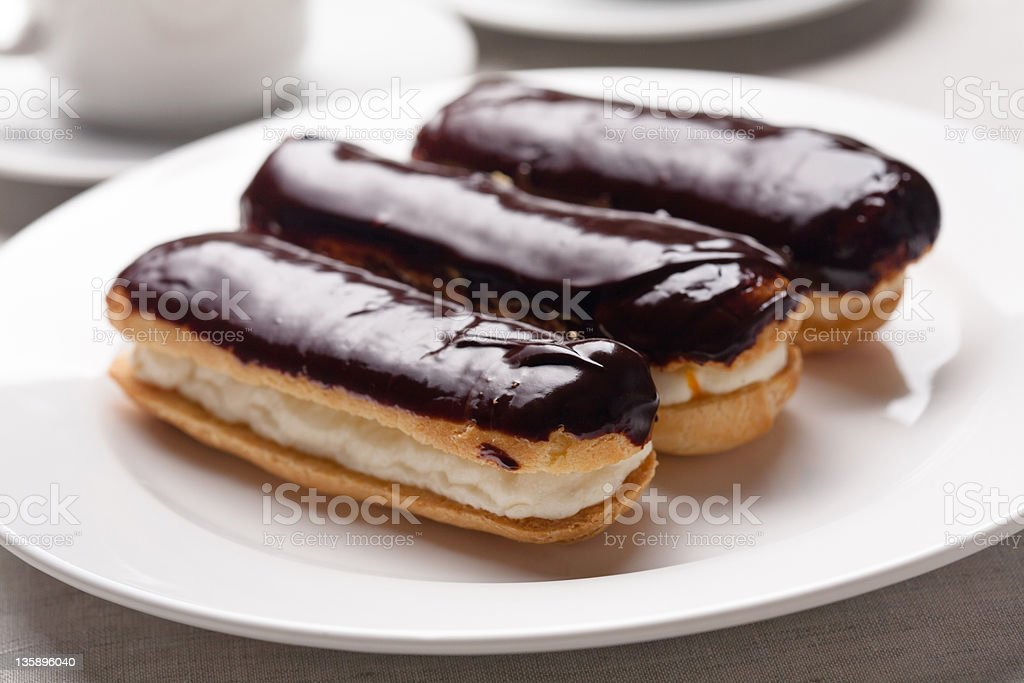 3 chocolate cream eclairs on a white plate stock photo
