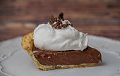 Close up of a slice of chocolate cream pie with whipped cream
