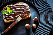 Chocolate cream spread on bread slice and hazelnuts on a dark black rustic plate with mit leaves on top