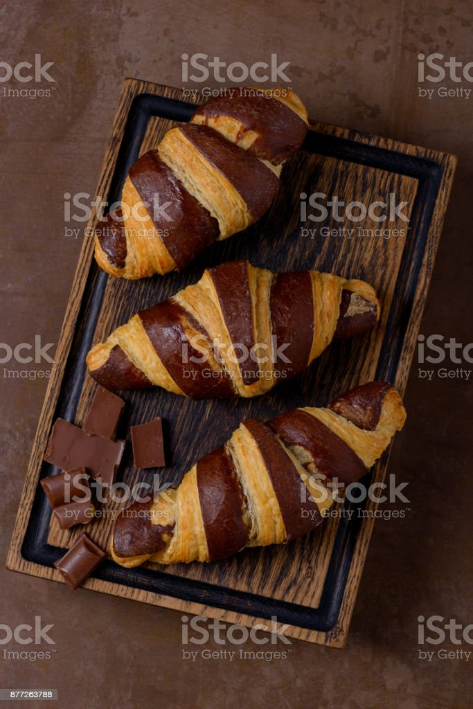 Chocolate croissant and chocolatier on table stock photo
