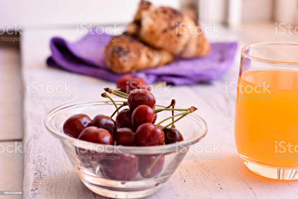 Chocolate croissant whit fresh squeezed orange juice and cherries at light wooden background/ Breakfast background/ Sweet breakfast/ Starting a day zbiór zdjęć royalty-free