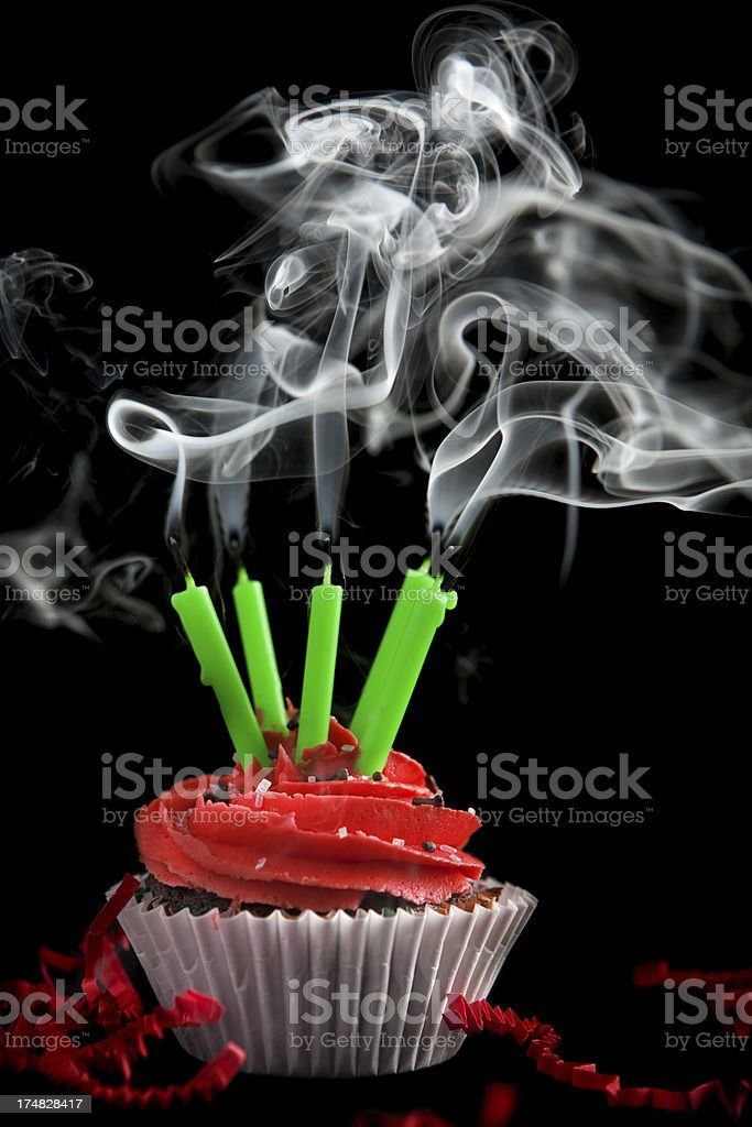 Chocolate Cupcake Red Frosting and Five Candles with Smoke royalty-free stock photo