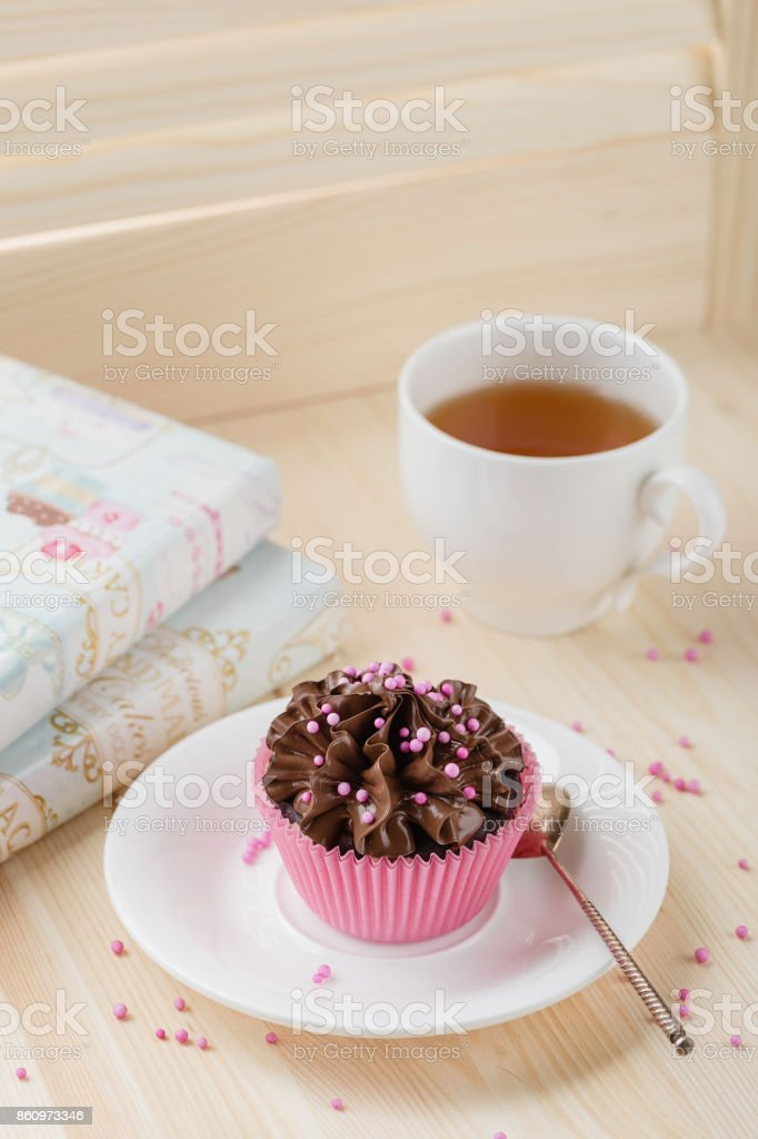 Chocolate cupcake with sprinkles in pink cup stock photo