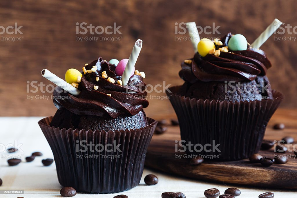Chocolate cupcakes on rustic wooden background stock photo