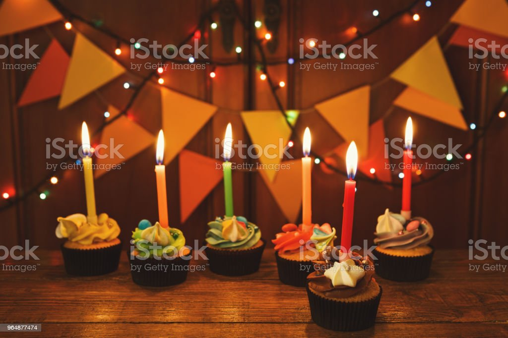 Chocolate cupcakes with candles against festive background royalty-free stock photo