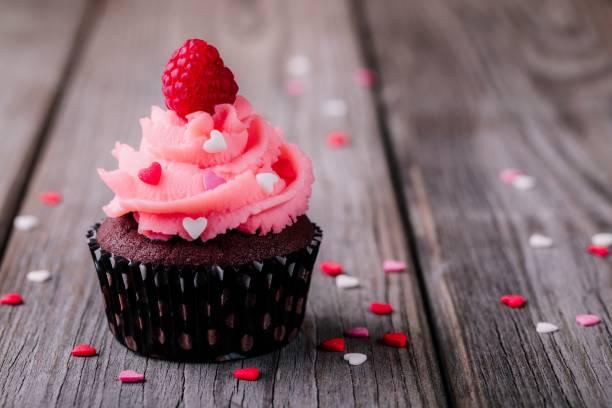 schokoladentörtchen mit rosa creme, zuckerherzen und frische himbeeren für den valentinstag - himbeerzuckerguss stock-fotos und bilder