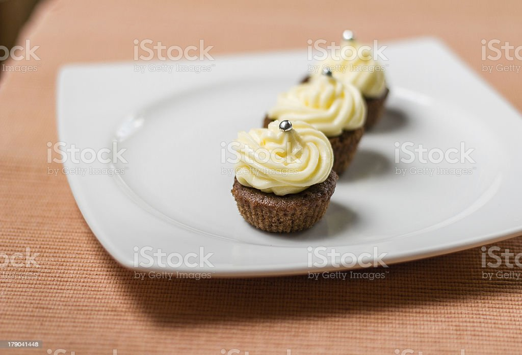 Chocolate cupcakes with silver sprinkles on white plate royalty-free stock photo