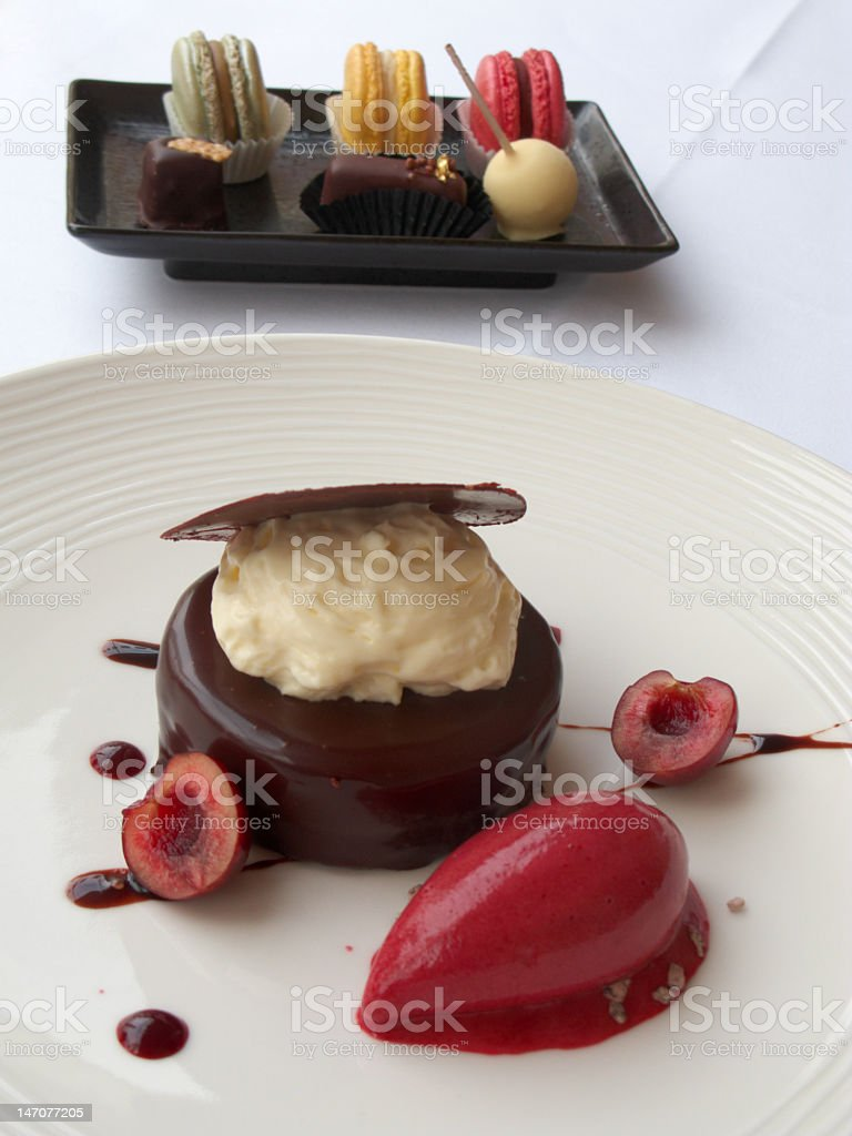 Chocolate dessert with cherry sorbet and artisan macaroon chocolates royalty-free stock photo