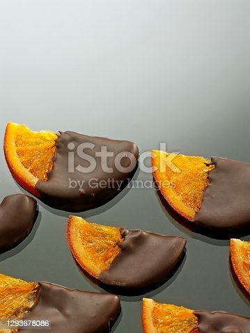 Chocolate dipped orange candies on gray background