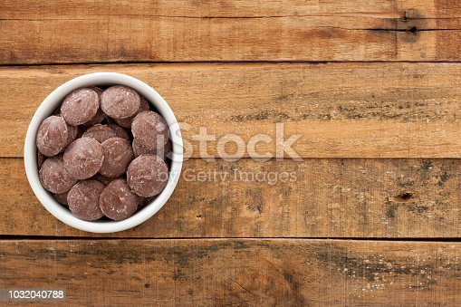 Top view of white bowl full of chocolate disks over wooden table