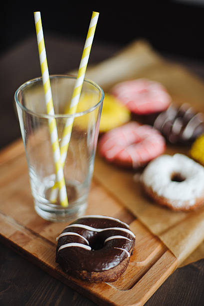 chocolate donut with glass close up - pone stock photos and pictures