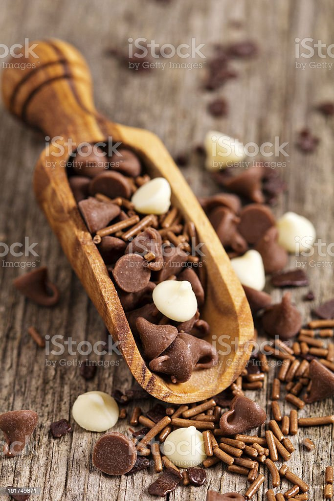 Chocolate drops and sprinkles in a wooden scoop royalty-free stock photo