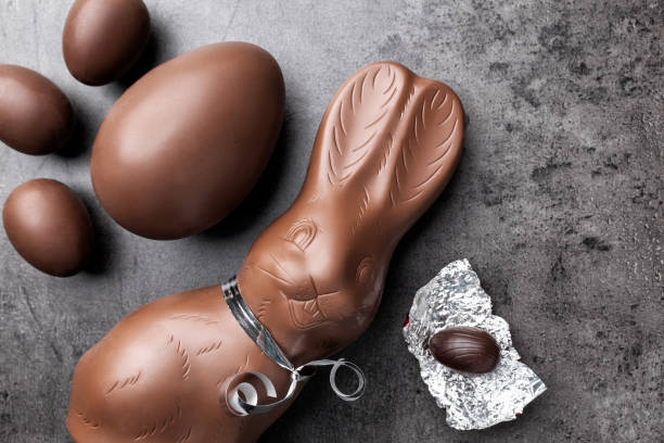 Chocolate Easter bunny and eggs on rustic background stock photo