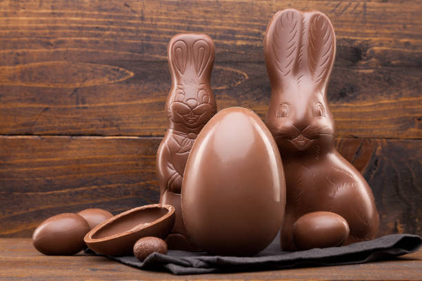 Chocolate Easter bunny, eggs and sweets on rustic background stock photo