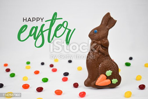 istock Chocolate Easter Bunny, Jelly Beans Candy and Happy Easter Text on White Background 1142537902