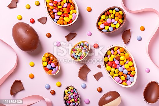 Chocolate Easter eggs and candy on concrete table, festive Easter background flat lay, copy space. Easter card with traditional Easter treats on pink table top.