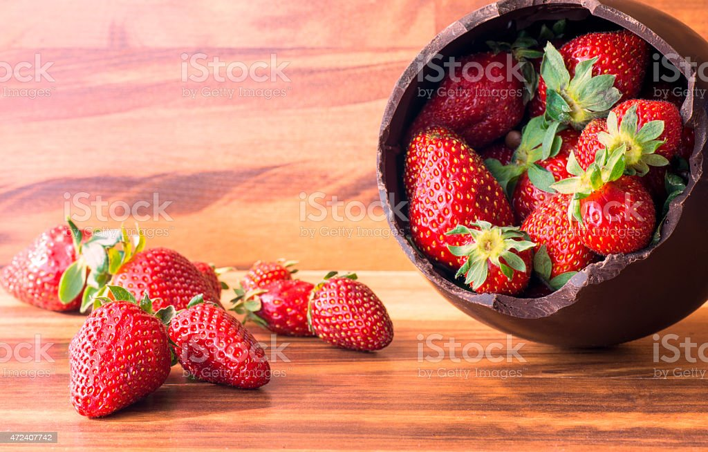 Chocolate Easter egg filled with strawberries stock photo