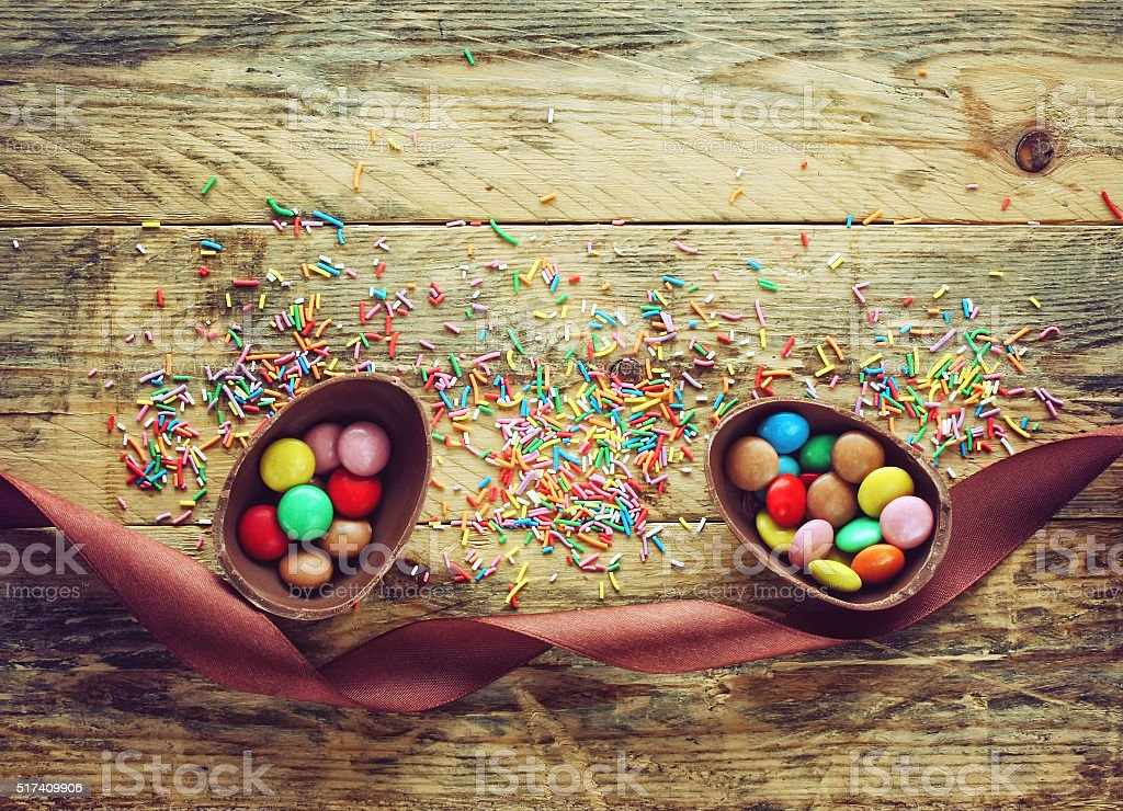 Chocolate Easter egg with candy and ribbon stock photo