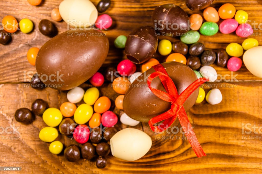 Chocolate easter eggs and multicolored candies on wooden table. Top view royalty-free stock photo